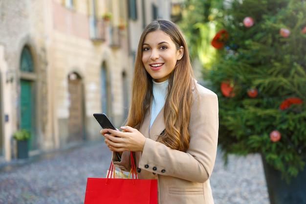 Красивая женщина моды с хозяйственными сумками, делая покупки онлайн с умным телефоном на улице во время рождества смотря камеру.