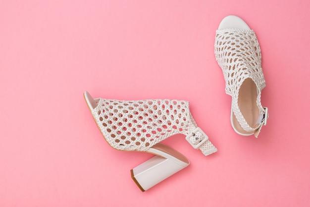ピンクの表面に美しいファッションの女性の夏の靴