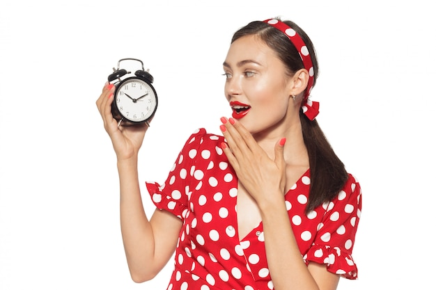 Beautiful and fashion young woman with a pin-up look holding a clock
