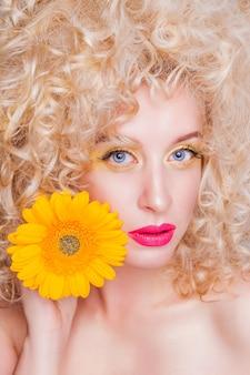 Красивая модная блондинка в стиле ретро с объемной фигурной прической
