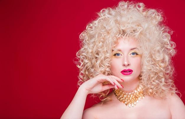 방대한 곱슬 헤어 스타일과 복고 스타일의 아름다운 유행 금발 소녀