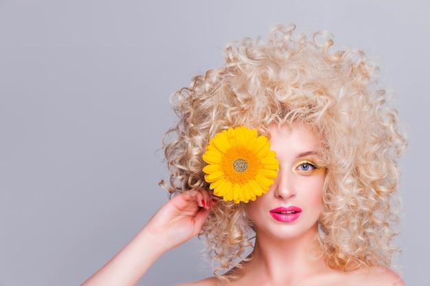 Красивая модная блондинка с объемной кудрявой прической