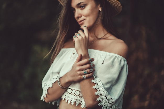 Beautiful fashionable boho chic woman in straw hat and in a white short blouse with silver turquoise jewelry