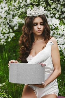 Beautiful and fashionable brown-haired model woman with gentle make-up and with stylish hairstyle and crown, in trendy satin lingerie, posing with the dove in the box outdoors at green forest