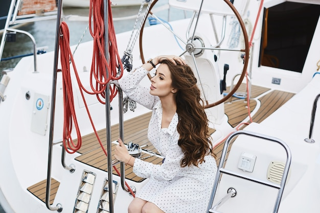 Beautiful fashionable brunette model girl in white short stylish dress adjusting her hairstyle, sits and posing on a yacht ship at the sea