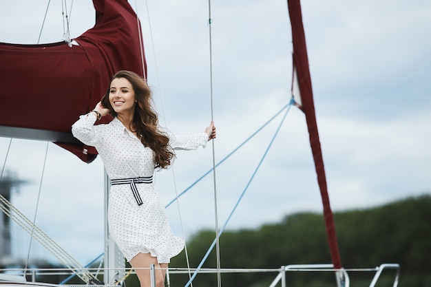 Beautiful fashionable brunette model girl in white short stylish dress smiling, adjusting her hairstyle and posing on a yacht ship at the sea