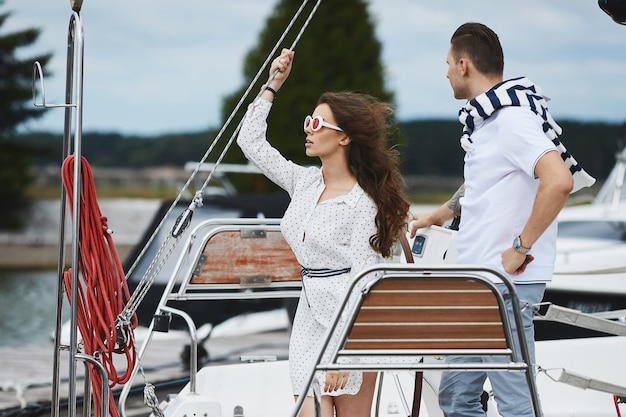 Beautiful fashionable brunette model girl in white short stylish dress and trendy sunglasses posing on a yacht ship at the sea