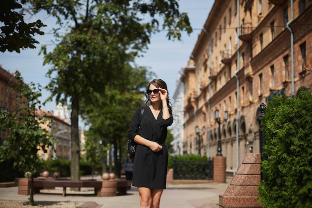 Beautiful and fashionable brunette model girl with the trendy backpack in a stylish black dress and in sunglasses walking by the spring city street