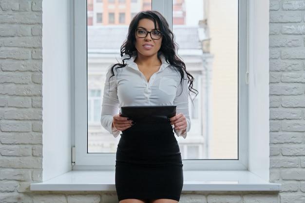 デジタルタブレットを持つ美しいファッショナブルなビジネス女性。髪型の女性
