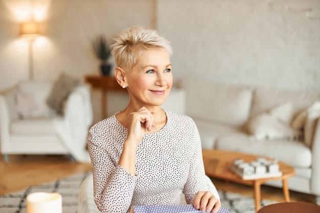 Красивая модная европейка лет пятидесяти, впитавшая взгляд, упаковывая новогодние подарки, обдумывая поздравления и пожелания, счастливо улыбаясь. праздник и праздничное настроение