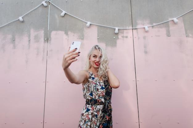 유행 드레스에 아름 다운 유행 소녀 파티에서 분홍색 벽 근처 전화에 셀카를 만든다