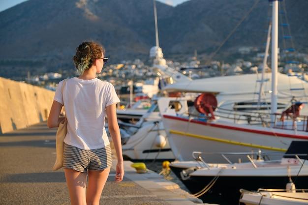 海の遊歩道、背面図、ヨットの桟橋に沿って歩く美しいファッショナブルな女の子のティーンエイジャー。山、海の背景に沈む夕日、コピースペース。レジャー、リゾート、美容、ファッション、若者のコンセプト