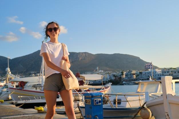 海の遊歩道、ヨットの桟橋に沿って歩く美しいファッショナブルな女の子のティーンエイジャー。山、海の背景に沈む夕日、コピースペース。レジャー、リゾート、美容、若者、ファッション、若者のコンセプト
