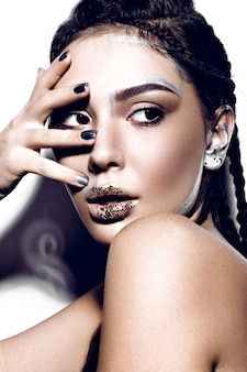 Beautiful fashionable girl with creative glitter make-up, hairstyle braids and sparkles on the lips