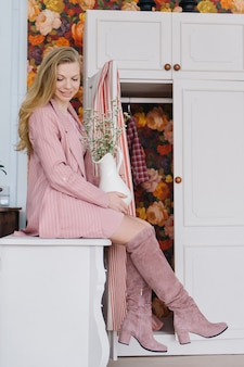 ピンクのパウダージャケットとブーツで長いブロンドの巻き毛を持つ美しいファッショナブルな女の子は、居心地の良いインテリアの引き出しの胸に座っています。手に花瓶に繊細な花。
