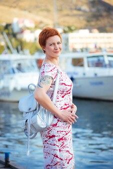 Красивая модная рыжеволосая женщина наслаждается морским отдыхом в яхт-клубе