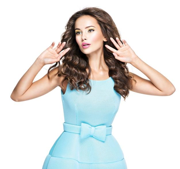 파란 드레스에 아름 다운 유행 여자입니다. 매력적인 패션 모델 흰색 배경에 포즈입니다.