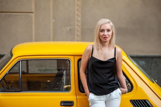 街の古い黄色いカリンの近くの美しいファッショナブルな女性