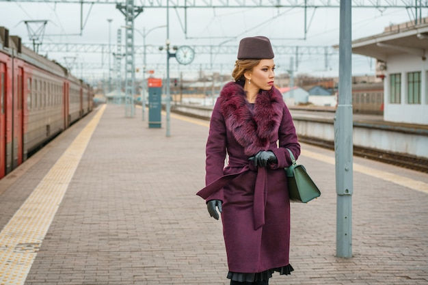 Beautiful fashionable woman on the platform waiting, gloomy autumn day