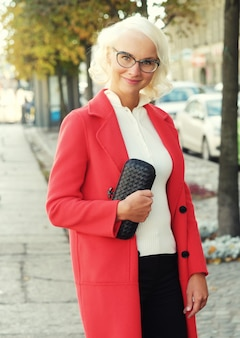 Beautiful fashionable woman standing on the city street. autumn day.