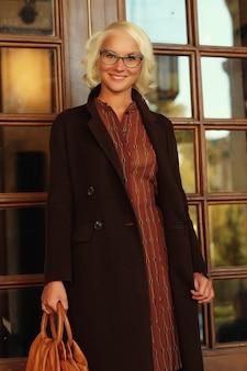 도시 거리에 서 있는 아름 다운 유행 여자입니다. 가을 날.