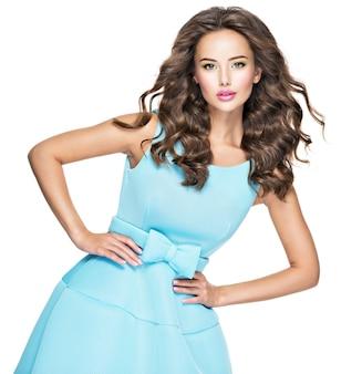 Bella donna alla moda con i capelli lunghi in abito blu. modello di moda attraente in posa su sfondo bianco.