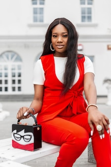 Beautiful fashionable young african woman with sexy lips in red stylish clothes posing near white building on street. cute black woman in fashion suit with vintage bag rests in city. beauty lady.