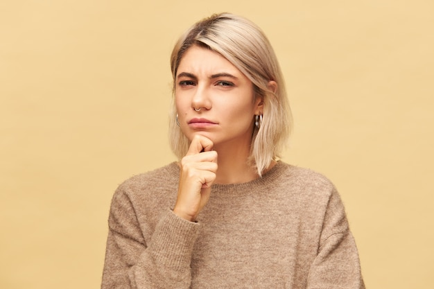 Beautiful fashionable young suspicious european female in cashmere pullover holding hand on her chin and staring with suspicion and mistrust, screwing up eyes. human facial expressions