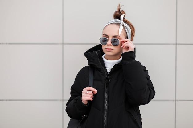 벽 근처 포즈를 취하는 그녀의 어깨에 검은 배낭 두건으로 세련된 검은 코트에 검은 안경에 세련된 헤어 스타일로 아름 다운 유행 젊은 여자 소식통. 미국 소녀.