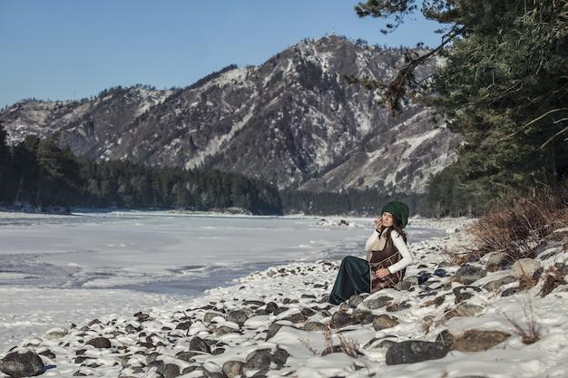 산과 강을 배경으로 겨울에 아름다운 세련된 젊은 여성