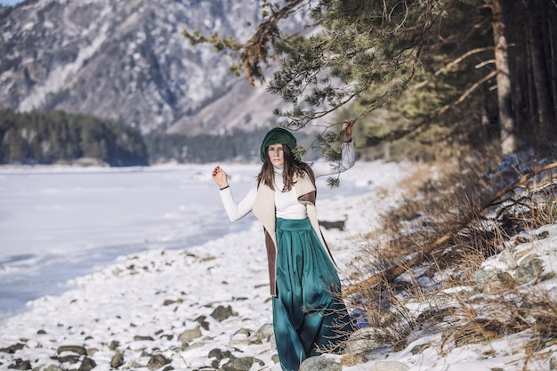 Beautiful fashionable young woman in winter on a background of mountains and rivers