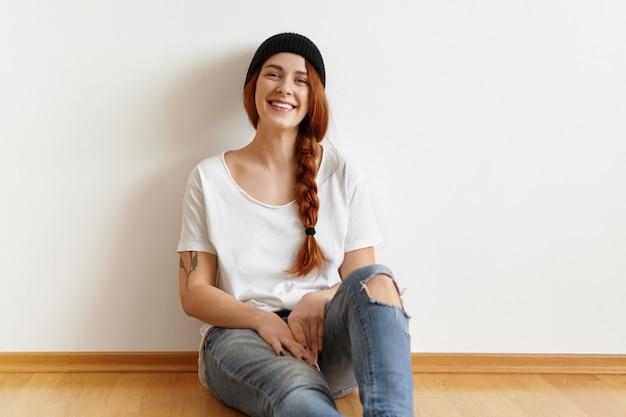スタイリッシュな帽子をかぶって幸せな笑顔で美しいファッショナブルな若い女性