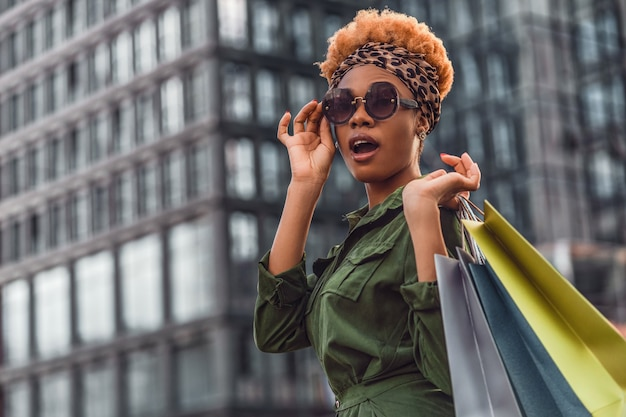 Beautiful and fashionable young woman with shopping bags standing on city street and looking away