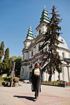 カトリック大聖堂に対してポーズをとって美しいファッショナブルな若い若い女性