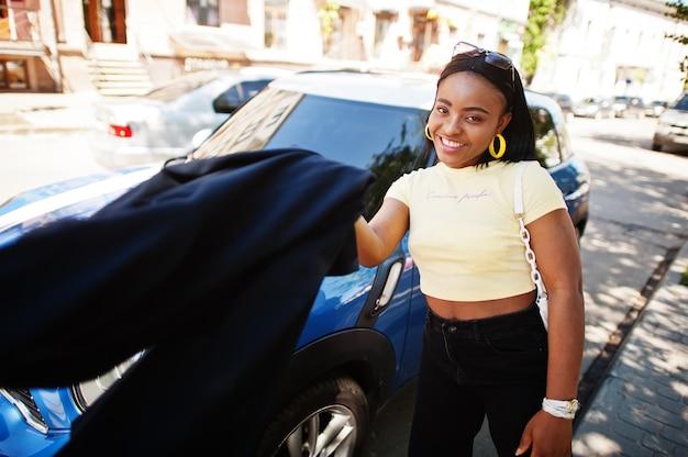 青い小さな都市の車に対して通りでポーズをとって美しいファッショナブルな若い若い女性