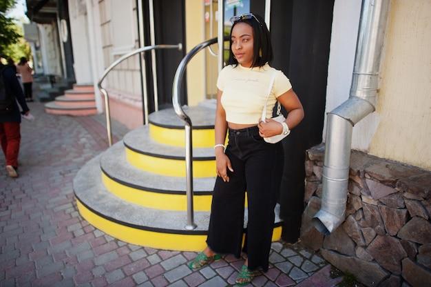 サングラスと黄色のトップと通りの階段でポーズをとって美しいファッショナブルな若い若い女性
