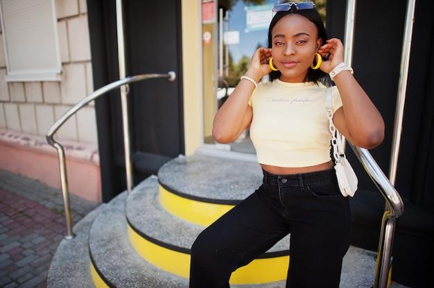 サングラスと黄色のトップと通りの階段でポーズをとって美しいファッショナブルな若い若い女性 Premium写真