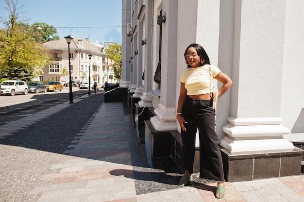 サングラスと黄色のトップでストリートでポーズをとる美しいファッショナブルな若い若い女性 Premium写真
