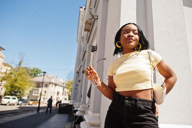 サングラスと黄色のトップでストリートでポーズをとる美しいファッショナブルな若い若い女性