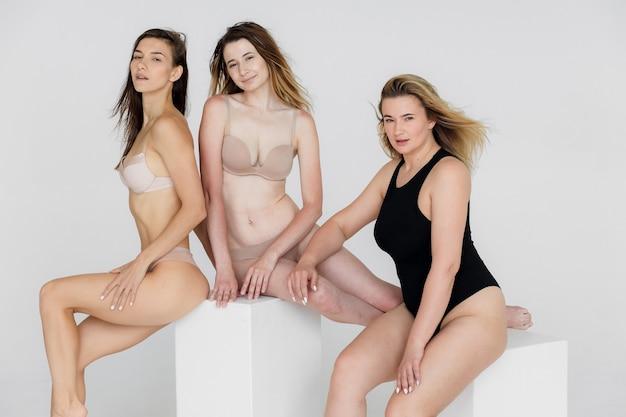 분홍색 배경에 검은 란제리를 입은 아름다운 뚱뚱한 소녀 다른 신체와 인종 고품질 사진을 가진 여성의 긍정적인 개념 그룹