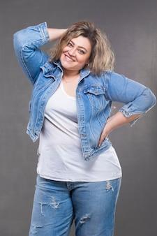 회색 배경에 데님 정장을 입은 아름다운 뚱뚱한 여자.