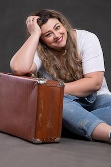 오래 된 복고풍 가방 데님 옷에 아름 다운 뚱뚱한 여자