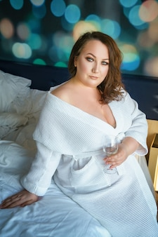 Beautiful fat woman sitting on bed , morning