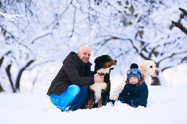 The beautiful father, son and dogs sitting on the snow