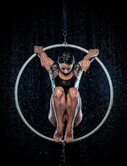 Красивый женский акробат, сидящий на симметричной позе в воздушном обруче под дождем на черном фоне.