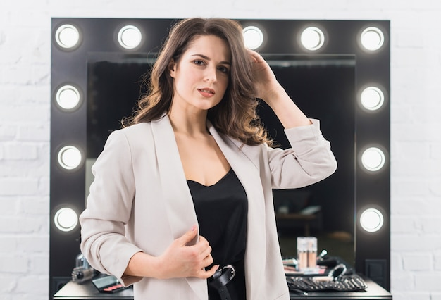 Beautiful female against makeup mirror