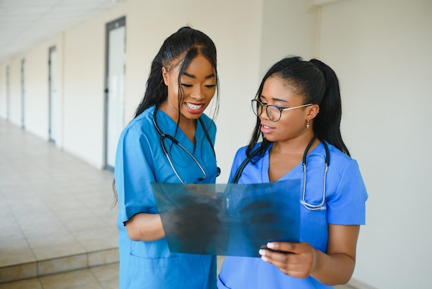 아름다운 여성과 잘 생긴 아프리카계 미국인 의사들이 엑스레이 사진을 검사하고 있고, 다른 두 명의 의사가 뒤에서 이야기하고 있다