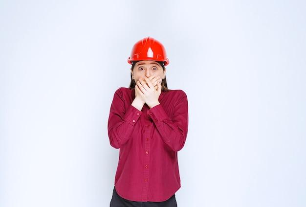 빨간색 하드 헬멧에 아름 다운 여성 건축가 뭔가 무서 워.