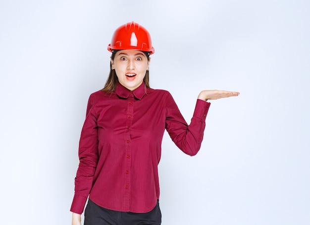 オープンスペースを立って保持している赤いヘルメットの美しい女性建築家。