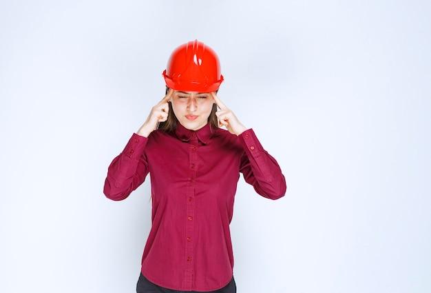立って、一生懸命考えている赤いヘルメットの美しい女性建築家。